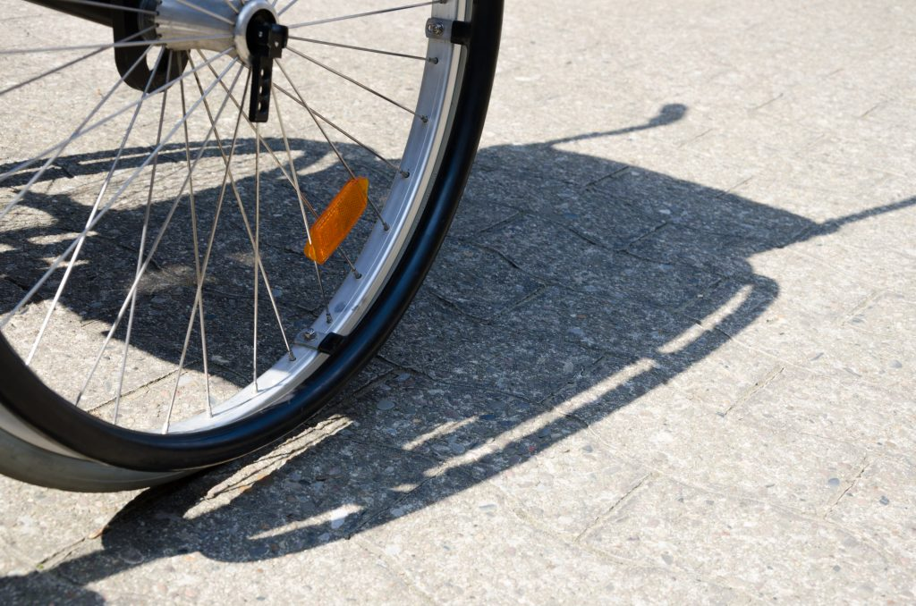 Ein Rollstuhlreifen und der Schatten eines Rollstuhls auf Pflasterstein. Foto von Konstanze Rosenbaum.
