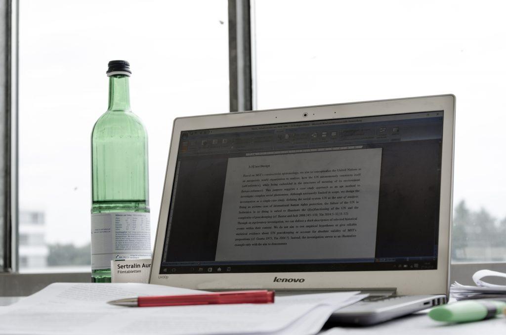 Ein Arbeitsplatz mit Laptop, Trinkflsche, Medikamentenpackung und Schreibwaren. Foto von Konstanze Rosenbaum.